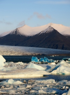 Amazing blue icebergs in the lagoon at Jökulsárlón. Breiðamerkurjökull glacier in the background