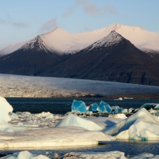 Amazing blue icebergs in the lagoon at Jökulsárlón. Breiðamerkurjökull glacier in the background