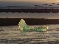 Iceberg floating out to sea under the Ring Road bridge at Jökulsárlón